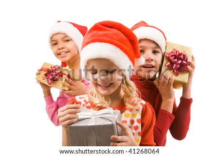 Happy girl with giftbox in hands looking at it with her friends at background - stock photo