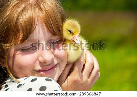 Happy girl with gosling - stock photo