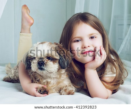 happy girl with her dog in bed at home - stock photo