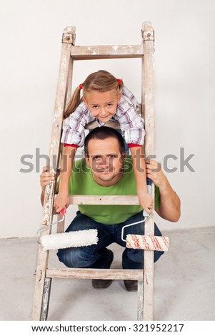 Happy girl with her father repainting the room - preparing the utensils - stock photo