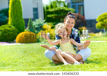 Happy girl with her mother sitting on the lawn in front new cottage - stock photo