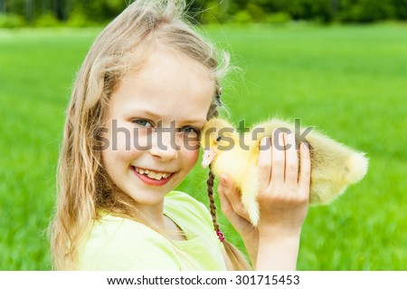 Happy girl with little gosling - stock photo