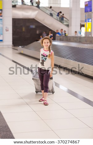 Happy girl with luggage inside airport going on vacations trip  - stock photo