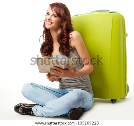 Happy girl with map and luggage and with big smile on her face - stock photo