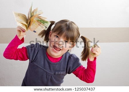 Happy girl with money in her hand - stock photo