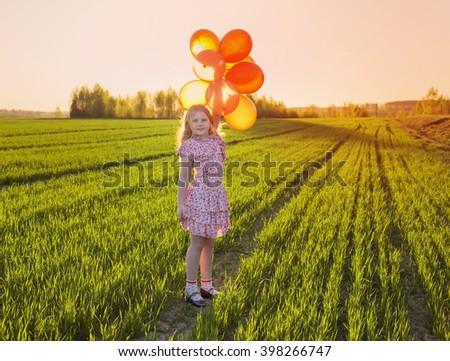 happy girl with orange balloons outdoor - stock photo