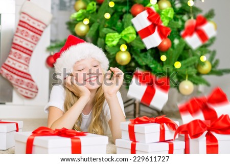 Happy girl with radiant face, smiling and enjoying christmas gift's fall. Little girl with Santa Hat , Christmas gifts boxes under illuminated Christmas Tree and chimney. Christmas card. - stock photo