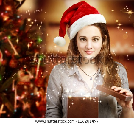 Happy Girl with Santa Hat Opening a Gift Box - stock photo