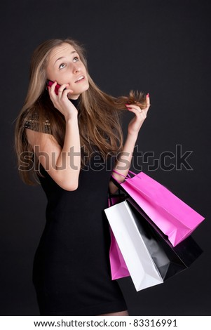 Happy girl with shopping talking on mobile phone photography studio - stock photo
