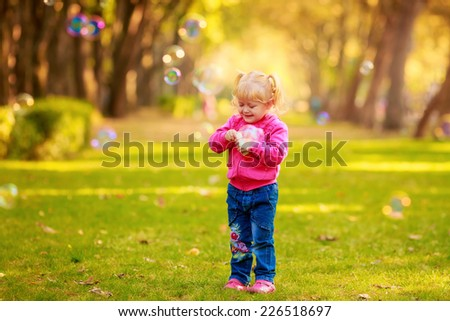 Happy  girl with soap bubbles in the park. play, run,  children's emotions - stock photo