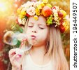 Happy Girl with wreath from flowers blows Soap Bubbles at Summer. Sun light. Happy Children - stock photo