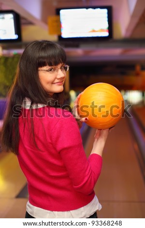happy girl with yellow ball stands back to camera in bowling club and preparing to throw - stock photo