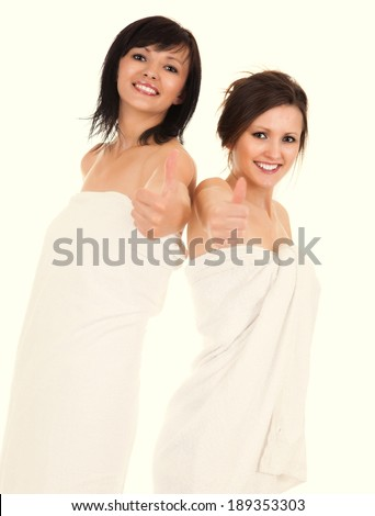 happy girlfriends with thumbs up in spa, white background - stock photo