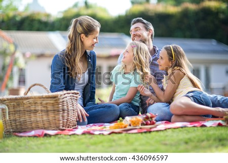 Happy girls and father looking at mother while sitting on blanket - stock photo