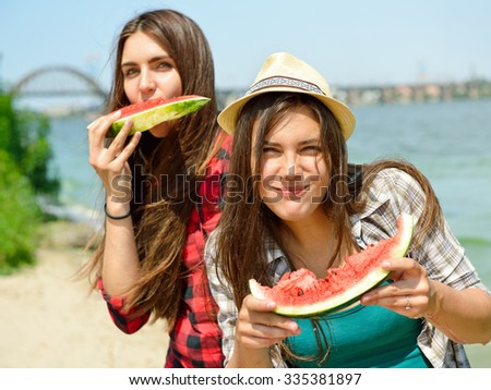Happy girls eating watermelon on the beach. Youth lifestyle. Happiness, joy, friendship, holiday, beach, summer concept. Young people having fun outdoor. - stock photo