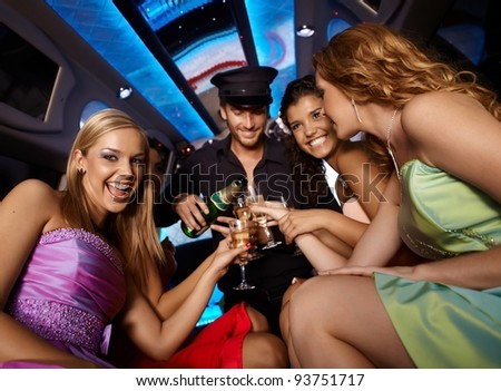 Happy girls having fun in limo, drinking champagne.? - stock photo