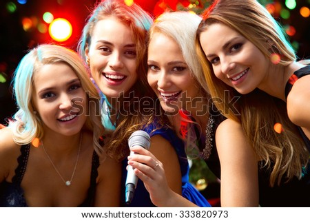Happy girls having fun singing at a party - stock photo