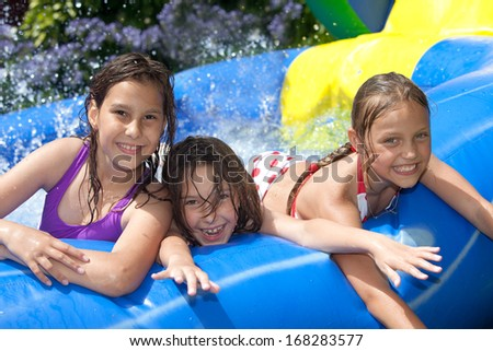 happy girls in inflatable pool - stock photo