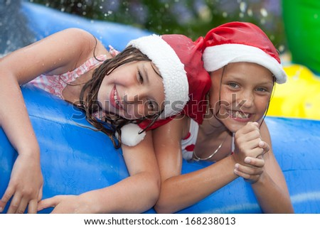 happy girls in inflatable pool wearing christmas hats - stock photo