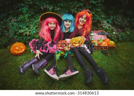 Happy girls in wigs and Halloween costumes holding pumpkins and sweets - stock photo