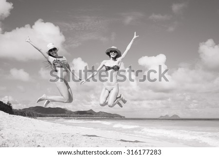Happy girls jumping for joy on the beach.  - stock photo