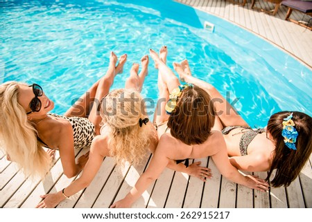 happy girls on the beach. beautiful girlfriends lie on white wooden floor near the pool and holding hands. girls lying on their backs - stock photo