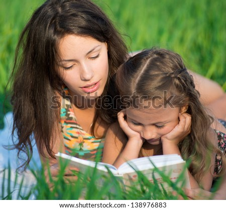 Happy girls reading book on green grass at spring or summer park picnic - stock photo