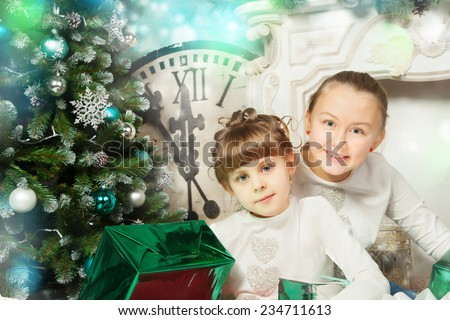 Happy girls sisters with presents while Christmas time - stock photo