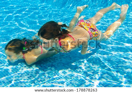 Happy girls swim underwater in pool and having fun, children on summer  vacation, kids sport concept  - stock photo