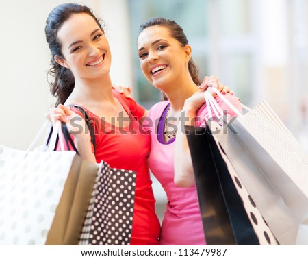happy girls with shopping bags in mall - stock photo