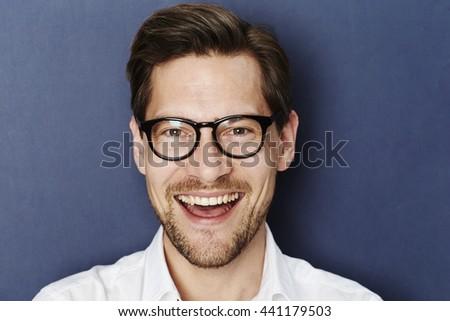 Happy glasses guy in blue studio - stock photo
