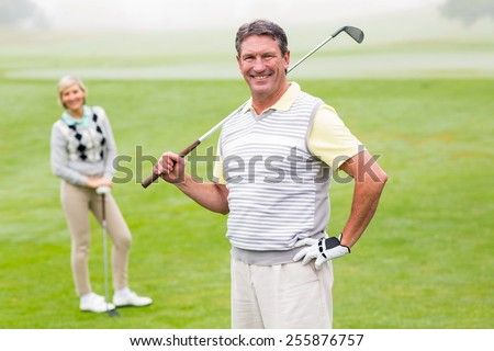 Happy golfer teeing off with partner behind him on a foggy day at the golf course - stock photo