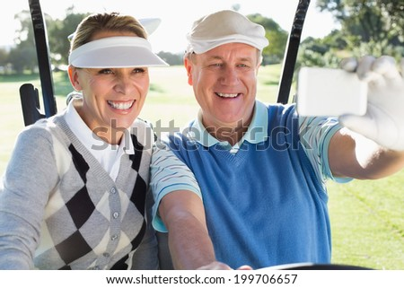 Happy golfing couple sitting in golf buggy taking a selfie on a sunny day at the golf course - stock photo