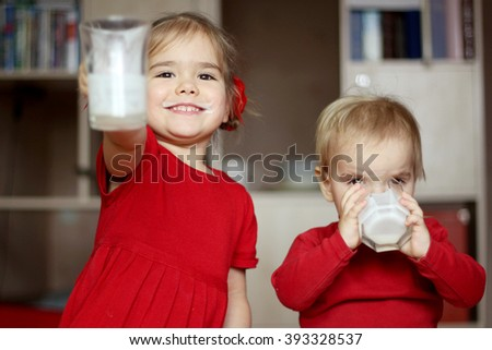 Happy gorgeous little girl with milk mustache showing an empty glass while her little cute brother drinking a glass of milk at home, food and drink concept, healthy food, indoor - stock photo