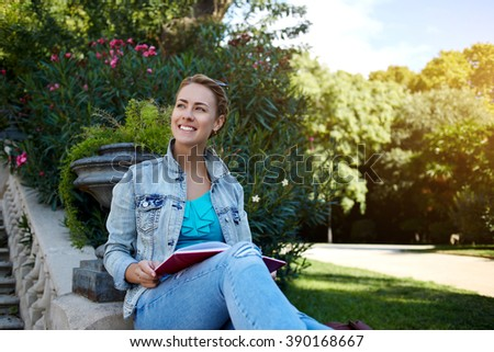 Happy gorgeous woman is enjoying beautiful warm day and spare time while is sitting in green nice park, young cheerful Caucasian female is smiling to someone while is relaxing outdoors with book - stock photo
