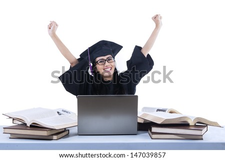 Happy graduate is raising her arms with laptop and books on white - stock photo