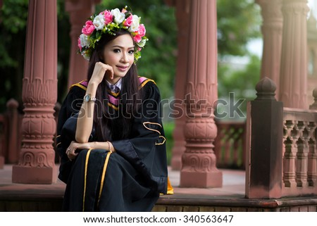 Happy Graduating  Woman In Gown Celebrating on Campus, female graduate,Woman standing out from a graduation - stock photo