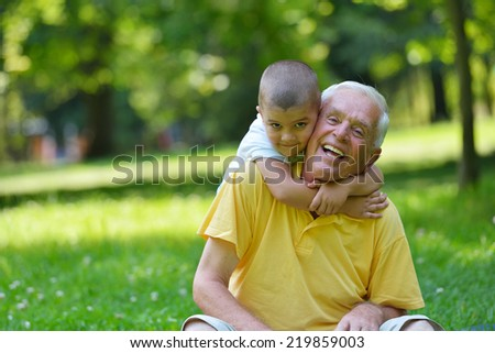 happy grandfather and child have fun and play in park - stock photo