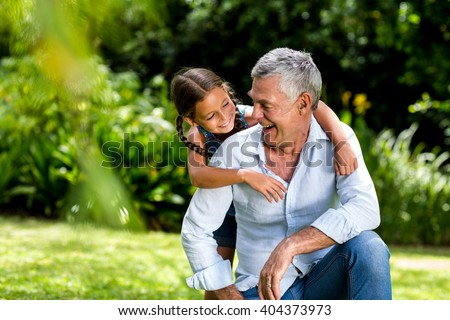 Happy grandfather and grandaughter playing at yard - stock photo