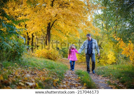 Happy grandfather and granddaughter in the autumn park - stock photo