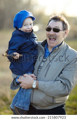 Happy grandfather and grandson having fun in autumn park - stock photo