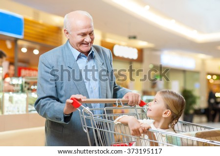 Happy grandfather and kid are shopping together. - stock photo
