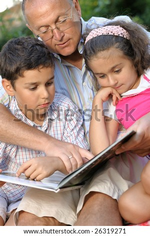 happy grandfather and kids reading book outdoors - stock photo