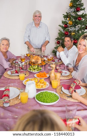 Happy grandfather carving the christmas turkey at the dinner table - stock photo