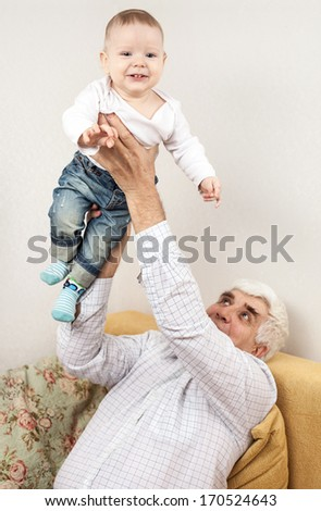 Happy grandfather holding grandson while sitting on sofa - stock photo