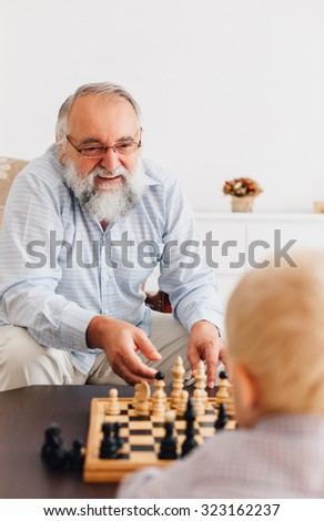 Happy grandfather playing chess with grandson - stock photo