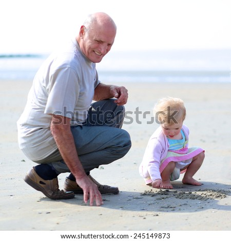 Happy grandfather playing with her granddaughter, cute toddler girl, at the beach drawing on the sand - happy retirement concept. Selective focus on child - stock photo