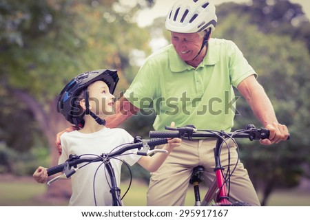 Happy grandfather with his granddaughter on their bike on a sunny day - stock photo