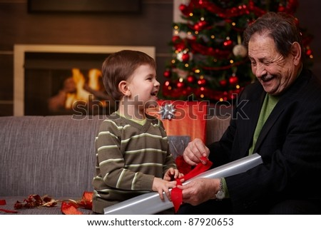 Happy grandfather wrapping gifts together with grandson at christmas, smiling. ? - stock photo