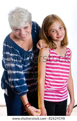 Happy Grandma and Grandchild with a measuring tape. - stock photo